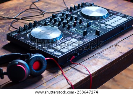Dj mixer with headphones on wooden table close-up. - stock photo