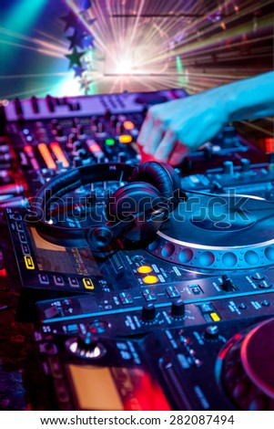 Dj mixes the track in the nightclub at party. In the background laser light show.  Headphones in foreground and DJ hands in motion - stock photo