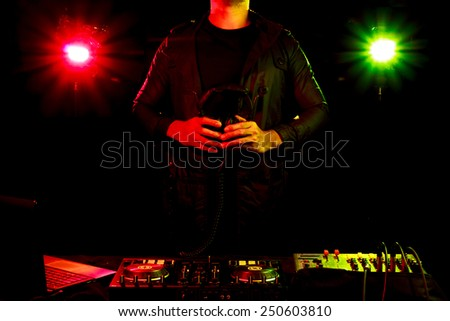 DJ mixes the track to play music in nightclub at party - stock photo