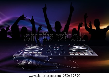 DJ mixes the track turntable to play music and crowd in nightclub at party - stock photo
