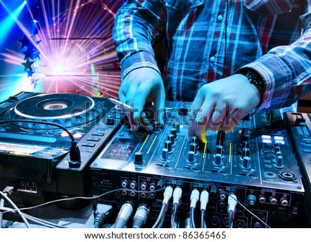 Dj mixes the track with a cigarette in his hand in the nightclub at a party. In the background laser light show