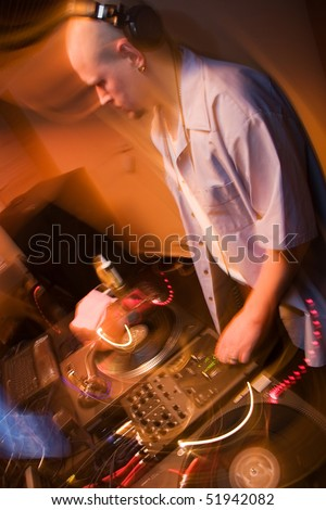 DJ mixing music on vinyl records on turntables in blurred motion yellow lights. Nightclub disc jockey at work. Musician playing the show in the club