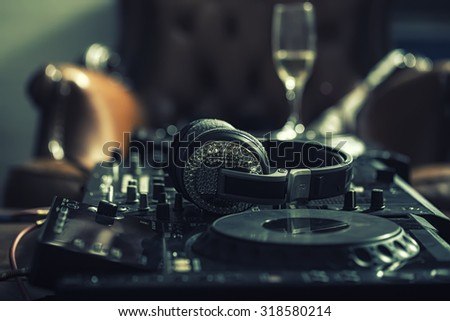 Dj musical mixer professional black console with many buttons and knobs and glamour headphones with pastes in night club or studio on brown leather sofa and wine glass background, horizontal picture - stock photo