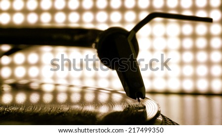 Dj needle stylus on spinning record, blur light background - stock photo