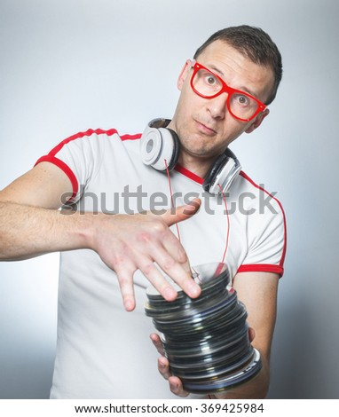 Dj or party young man holding lot cds against gray background - stock photo