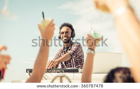 Dj playing at the beach party. Concert outdoor, with people raising drinks and hands to the sky. Entertainment and people concept - stock photo