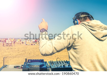 Dj playing music at a beach party - stock photo