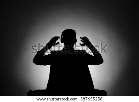 DJ playing music at mixer in dark - stock photo