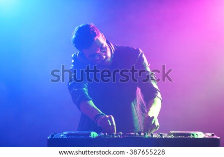 DJ playing music at mixer on colorful foggy background - stock photo