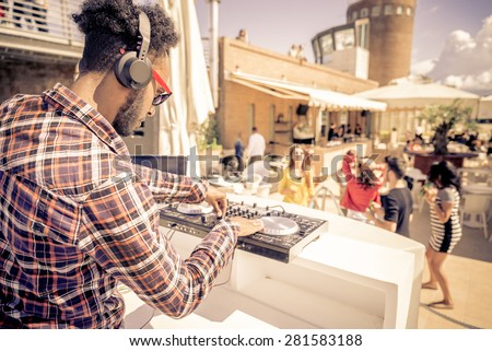 Dj playing trendy music in a open air club - People dancing and partying while the disc jockey mixes two song tracks in the console at a summer concert  - stock photo