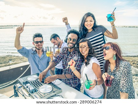 Dj playing trendy music in a open air club - People dancing and partying while the disc jockey mixes two song tracks at at summer concert - stock photo