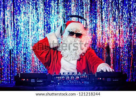 DJ Santa Claus mixing up some Christmas cheer. Disco lights in the background. - stock photo
