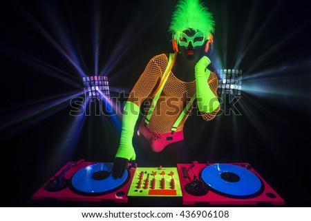 dj sexy male disco dancer play records in UV costume - stock photo