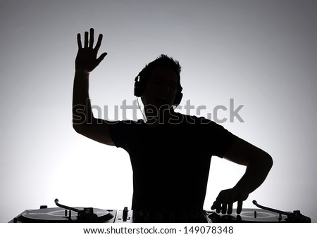 DJ silhouette. Silhouette of DJ gesturing and spinning on turntable - stock photo