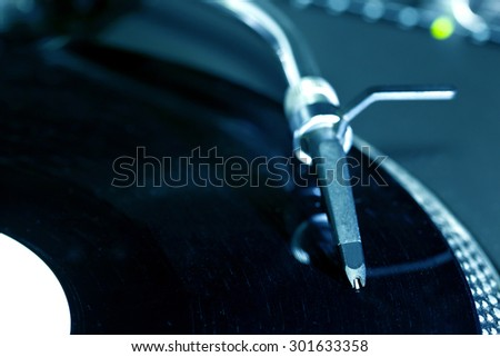 Dj turntable needle and on vinyl record  - stock photo