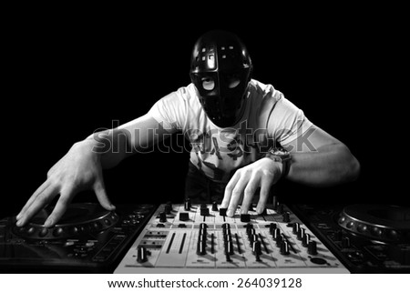 Dj with mask mixes the track in the nightclub at party - stock photo