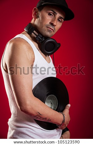 DJ with Scarfs and tatoos in front of a red background