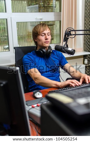 Dj working in front of a microphone on the radio - stock photo