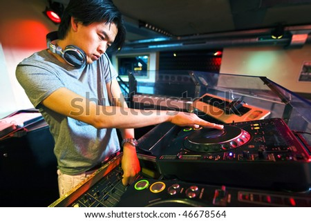 DJ working on the faders and turntables during his act in a club - stock photo