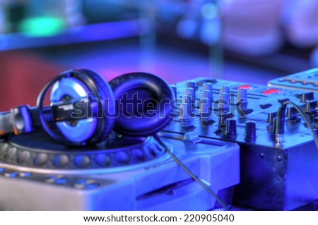 Djs table with audio equipment in the crowded club - stock photo