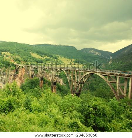 Djurdjevica Tara Bridge is a bridge over the Tara River in Montenegro, Europe. Square toned image, instagram effect - stock photo
