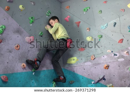 DNEPROPETROVSK, UKRAINE - APRIL 11, 2015: Boy trains during the open bouldering festival Dnepr Montana Kids. The festival organized by the climbing wall Montana and the association of extreme sports - stock photo
