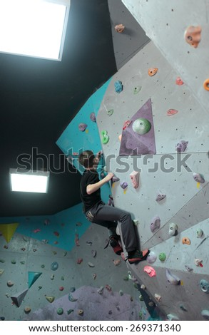 DNEPROPETROVSK, UKRAINE - APRIL 11, 2015: Boy trains during the open bouldering festival Dnepr Montana Kids. The festival organized by the climbing wall Montana and the association of extreme sports