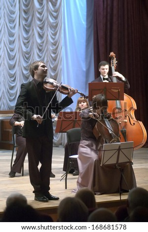 DNEPROPETROVSK, UKRAINE - DECEMBER 24: Violinist Ostap Shutko and Academic Symphony Orchestra perform CHRISTMAS EVE at the Philharmonic on December 24, 2013 in Dnepropetrovsk, Ukraine