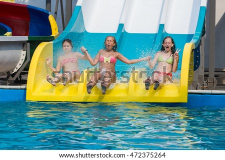 Dnepropetrovsk, Ukraine - July 30, 2016, Aquapark,Three children on the water slide at a water park, and hands up. Summer rest.