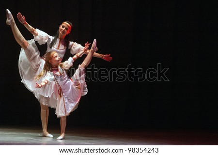 "DNEPROPETROVSK, UKRAINE - MARCH 12: Ira Booth, age 8 years old, and Tatiana Booth perform ""February. Keepers of the heat."" on March 12, 2012 in Dnepropetrovsk, Ukraine."