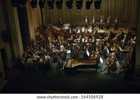 DNEPROPETROVSK, UKRAINE - NOVEMBER 25: Pianist Paul Kachnov and Symphonic Orchestra - conductor Natalia Ponomarchuk perform Tchaikovsky's First Concerto on November 25, 2013 in Dnepropetrovsk, Ukraine