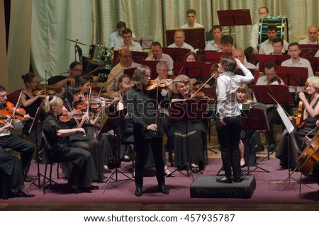 DNIPRO, UKRAINE - JULY 1, 2016: Famous Violinist Dmitry Tkachenko and Academic Symphony Orchestra - main conductor Natalia Ponomarchuk perform at the 