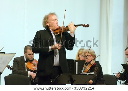 DNIPROPETROVSK, UKRAINE - DECEMBER 13, 2015: Famous conductor and violinist Michael Guttman (Belgium) and members of the Symphony Orchestra perform at the Regional Philharmonic - stock photo