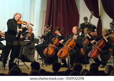 DNIPROPETROVSK, UKRAINE - DECEMBER 13, 2015: Famous conductor and violinist Michael Guttman (Belgium) and members of the Symphony Orchestra perform at the Regional Philharmonic