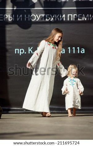 DNIPROPETROVSK, UKRAINE - SEPTEMBER 10: Gleb and Pauline Bulgarin, ages 2 and 11 years old, represent the author's clothes Pauline  BLOOMING COUNTRY on September 10, 2011 in Dnipropetrovsk, Ukraine