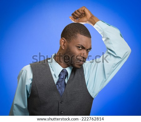 Do I stink? Young man smelling sniffing his armpit something smells bad foul odor isolated blue background. Negative human facial expression feeling body language perception. Personal hygiene concept - stock photo