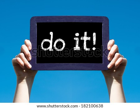 Do it ! Woman holding blackboard over blue background with text Do it ! - stock photo