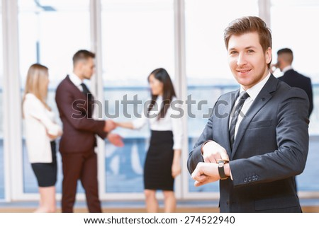 Do not be late for meeting.  Young business man standing in foreground smiling and pointing at his clock, his co-workers discussing business matters in the background - stock photo