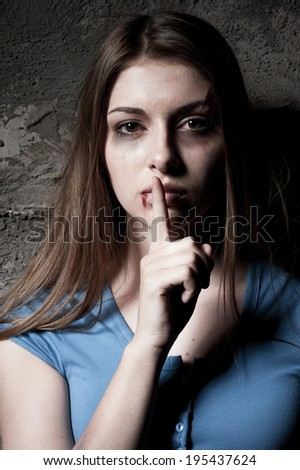 Do not be silent! Young beaten up woman looking at camera and holding finger on mouth while standing against dark wall - stock photo