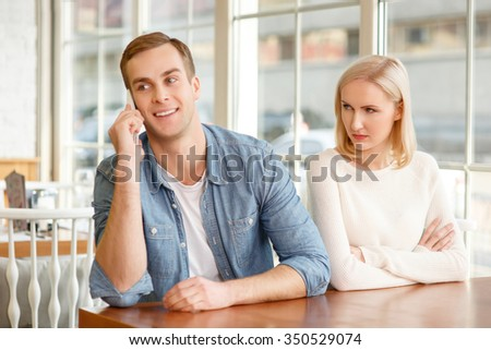 Do not cause jealousy. Pleasant happy young man talking on mobile phone and sitting in the cafe with his sweetheart.  - stock photo