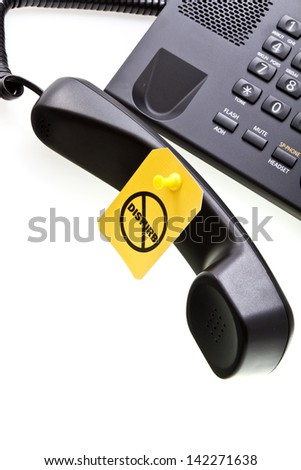 Do not disturb label with a thumbtack and office phone with a phone tube. Do not disturb with your calls concept. Isolated on white. - stock photo