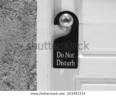 Do not disturb sign hang on door knob and stone wall. - stock photo