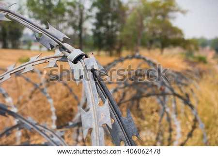 Do not enter the restricted area and locked by stringing barbed wire around. Re-enactment recreation of prison walls and prison bars with chain link fence of barbed razor wire and prison cell bars. - stock photo