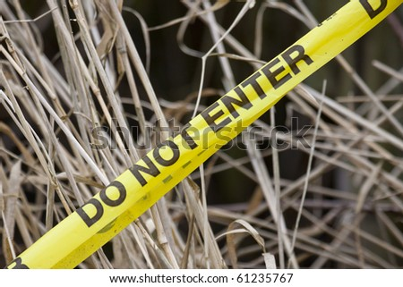 Do not enter yellow tape with a dry grass background - stock photo