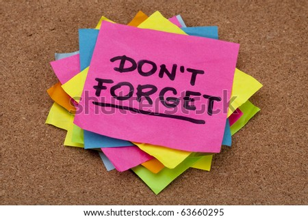 do not forget reminder - a stack of colorful sticky notes on cork bulletin board - stock photo