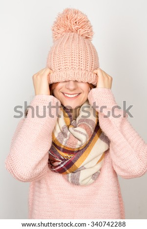 Do not forget to have fun. Young cute winter woman having fun pulling her woolen hat down her eyes - stock photo