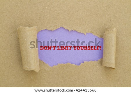 DO NOT LIMIT YOURSELF message written under torn paper. - stock photo