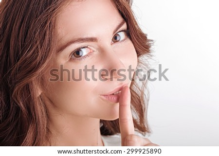 Do not make noise. Portrait of pleasant upbeat girl holding index finger in front of her mouth and looking straight while keeping silence