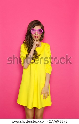 Do Not Tell Anyone. Beautiful young woman in yellow mini dress and pink heart shaped sunglasses holding finger on her lips telling you to hush. Three quarter length studio shot on pink background. - stock photo