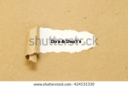 Do's and Don't's Message written under torn paper. - stock photo